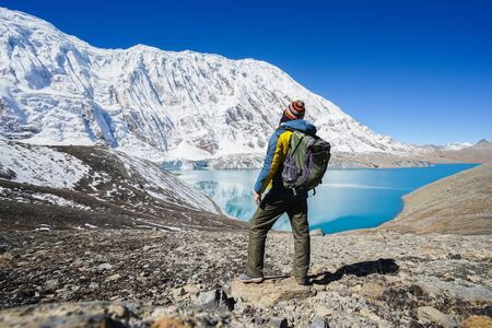 Travel and hikking concept: Trekker with backpack on Tilicho lake. Its 4900m above sea level. Snowly peaks of mountains and Tilicho lake on background.