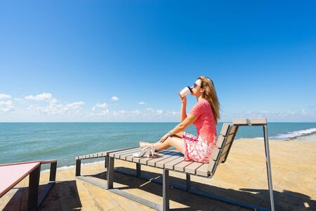 Young beautiful woman sitting on the beach chair with take off shoes and drink coffee.