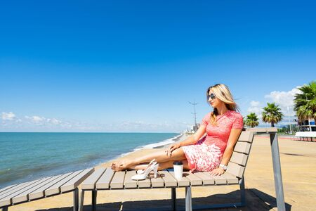 Young beautiful woman in red dress sitting on beach chair with shoes, coffee and looking on blue sea and sky.