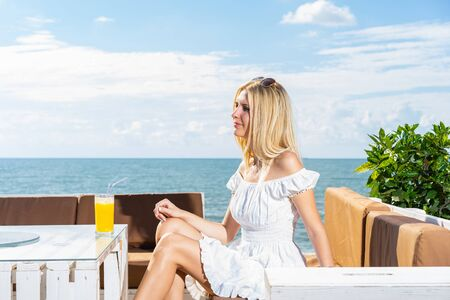 Young beautiful woman with orange juice sitting in the beach cafe. Standard-Bild