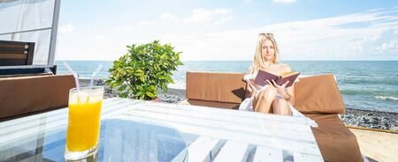 Young beautiful woman sitting on the beach cafe with orange juice and reading book. Banner edition. Focus on woman. Standard-Bild
