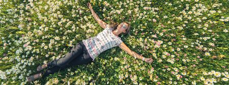 Young beautiful woman relaxing in the field with flowers. Overhead aerial view. Banner edition.