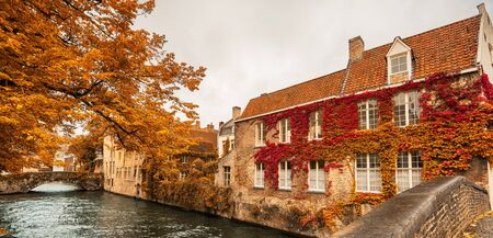 Panoramic view of beautiful canal with bridge and houses of Brugges, Belgium in autumn. Banner edition. Selective focus. Standard-Bild