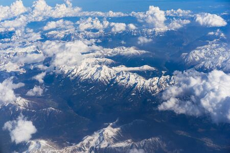 Aerial view of snowy Alps mountains with clouds. Standard-Bild