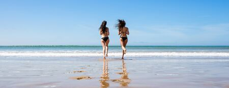 Two young women in swimwear running on the beach. Back view. Hair in motion view. Banner edition.