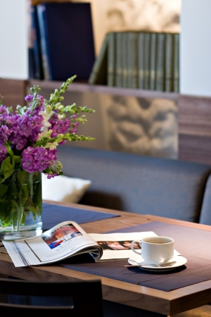 Coffee cup on table with fresh magazine and flowers photo