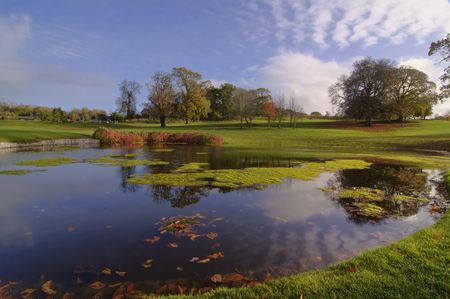 golf course course park pond by trees and blue sky Stock Photo