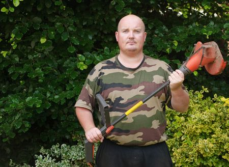 hedging: close up of male holding electrical hedge cutter trimmer garden