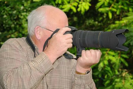 long range: closeup image of senior using a long range zoom lens