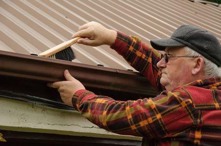 gouttière: senior masculin � l'abri de nettoyage de goutti�res avec pinceau