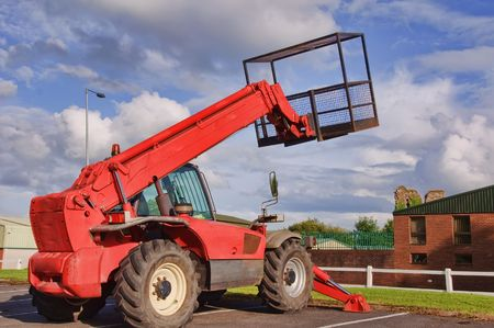 red mobile cherry picker into blue sky