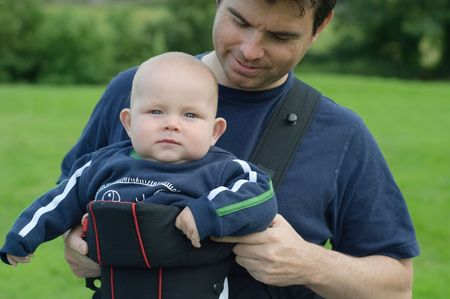 father helping son into baby carrier sling