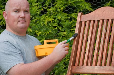 refurbish: male outside garden painting deck chair Stock Photo