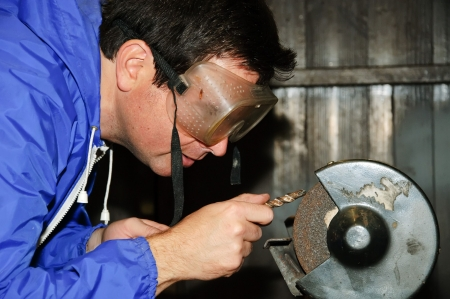sharpen: picture of male grinding sharp a drill bit