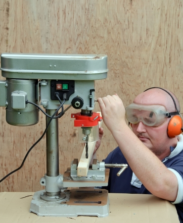 hand drill: picture male using a drill press on wood