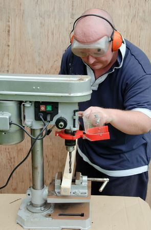 picture male using a drill press on wood photo