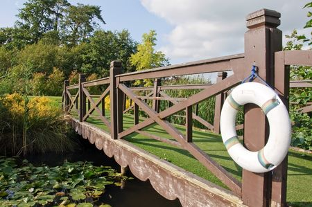bridge over water: wooden bridge over water with life ring