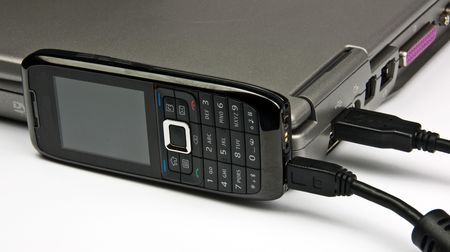 photo concept phone connected to laptop via usb cable photo