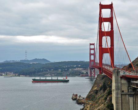 photo of golden gate bridge with ship sailing photo