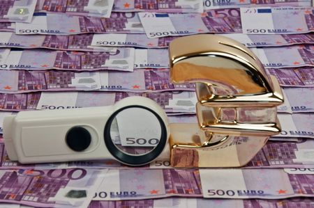 photo of 500 euro bills and gold euro symbol with magnify glass photo