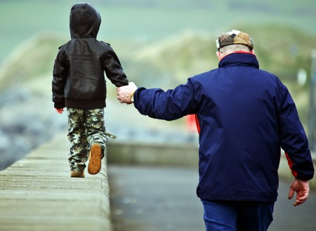 father and son walking hand in hand photo