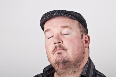 'eyes shut: photo of a middle age male portrait on off white backdrop Stock Photo