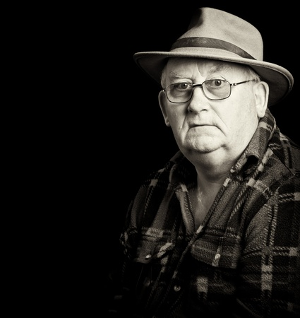 senior male retired wearing glasses and hat photo