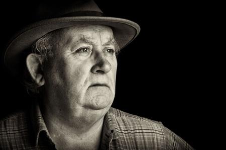 hombre viejo: Hombre Foto principal se retir� con un sombrero sobre fondo negro Foto de archivo