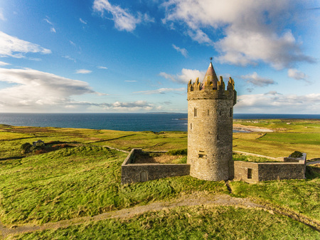 doolin: Aerial Famous Irish Tourist Attraction In Doolin, County Clare, Ireland. Doonagore Castle is a round 16th-century tower Castle. Aran Islands and along The Wild Atlantic Way.