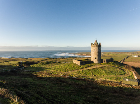 aran: Epic Aerial Scenic Irish Castle landscape view from Doolin in County Clare. Famous tourist attraction along the wild atlantic way Ireland. Aran islands coastal beach in the distance.