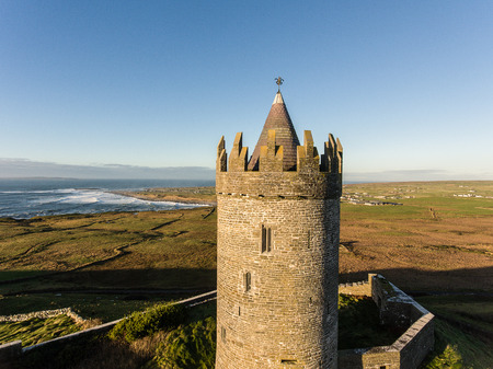 irish countryside: Epic Aerial Scenic Irish Castle landscape view from Doolin in County Clare. Famous tourist attraction along the wild atlantic way Ireland. Aran islands coastal beach in the distance.