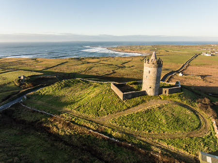 Epic Aerial Scenic Irish Castle landscape view from Doolin in County Clare. Famous tourist attraction along the wild atlantic way Ireland. Aran islands coastal beach in the distance.