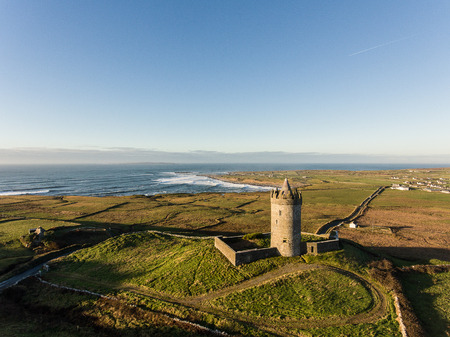 doolin: Epic Aerial Scenic Irish Castle landscape view from Doolin in County Clare. Famous tourist attraction along the wild atlantic way Ireland. Aran islands coastal beach in the distance.