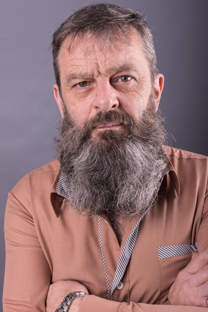 Photo of an angry grumpy old man looking very displeased. Male man with long beard on his face. Close up face looking into the camera.