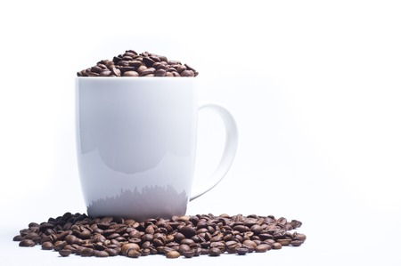 Coffee beans poured into the mug and around her on white background Stock Photo