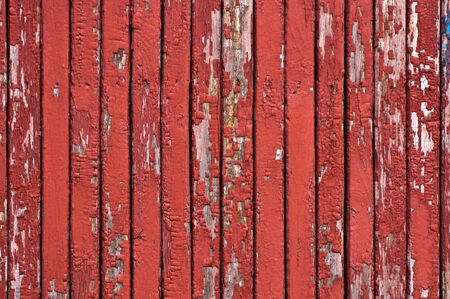 Wood planks, planks painted in red. The paint was peeling. Vertically