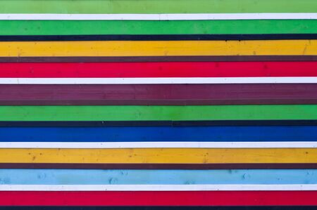 Striped colorful background made of wooden planks painted. The background image