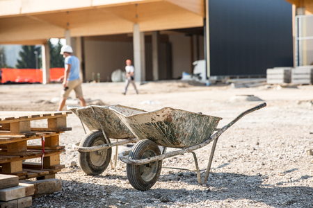 Two wheelbarrows in front of a construction site for small business premises. Property construction, small scale enterprise, expanding property concept.
