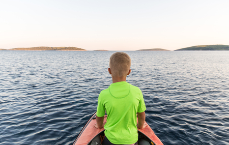 Brothers on a new adventure with father on a kayaking trip to a near by island to sleep under the stars. Concept photo of a family quality time, father and sons bond.