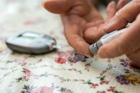 Ltere Frau überprüft ihr Zuckerniveau mit glucometer. Standard-Bild - 63709041