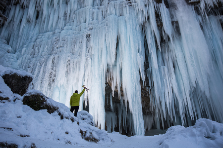Ice climber is checking frozen waterfall for the next extreme outdoor adventure. Reaching, planning, out of comfort zone, dedication concept photo.