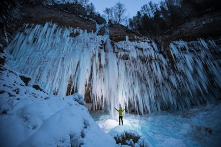 crampon: Ice climber is checking frozen waterfall for the next extreme outdoor adventure. Reaching, planning, out of comfort zone, dedication concept photo.