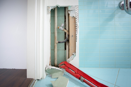 Hidden leaks in heating or watter supply can cause rot and other damage if left untreated. DIY, plumbing, water leak, home repair concept photo. Standard-Bild