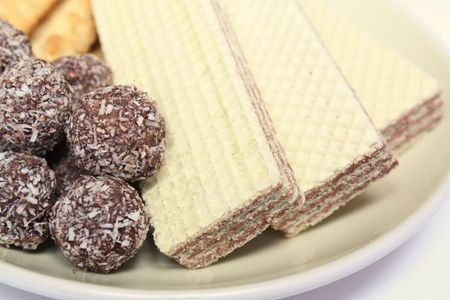 Various confectionery on plate, chocolate balls, wafer witch chocolate layers and cookies on white background photo