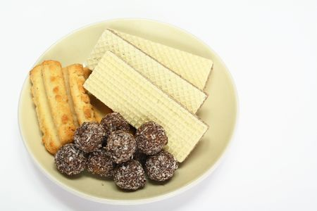 Various confectionery on plate, chocolate balls, wafer witch chocolate layers and cookies on white background Stock Photo - 7394156