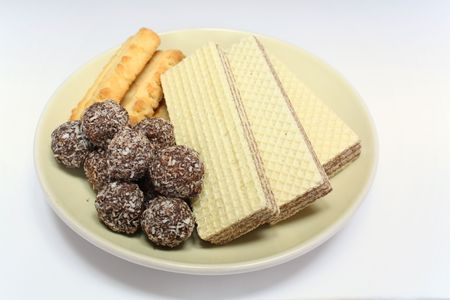 Vaus confectionery on plate, chocolate balls, wafer witch chocolate layers and cookies on white background Stock Photo - 7394159