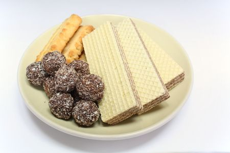 Various confectionery on plate, chocolate balls, wafer witch chocolate layers and cookies on white background Stock Photo - 7394158