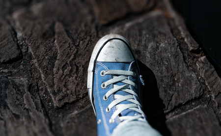 Sneaker shoes with blurred picture border and cobblestones in the background Stock Photo