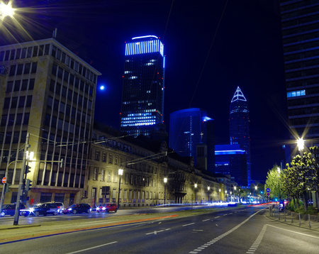 Frankfurt skyline with cars, skyscrapers and lights at night in a gloomy atmosphere and cold blue colors at Frankfurt in the state of Hesse in Germany