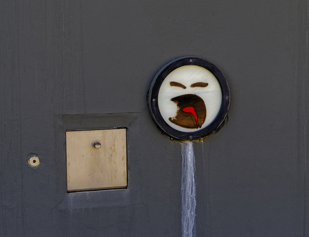 Sad smiley on a gray wall with outflow